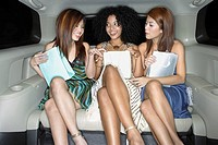 Three women in backseat of limousine with bags