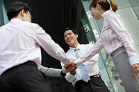 Four businesspeople outdoors with hands together in circle