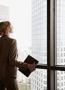 Businesswoman in corridor looking out large window
