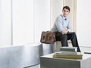 Businessman sitting in office lobby waiting