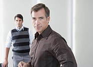 Two businessmen in boardroom looking at camera