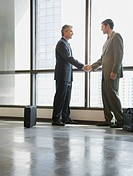 Two businessmen shaking hands in corridor by large windows