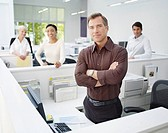 Four businesspeople in office looking at camera