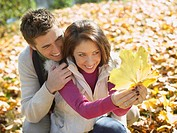Couple outdoors looking at a leaf