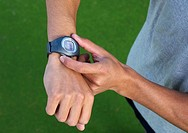 Man´s hands using wristwatch outdoors
