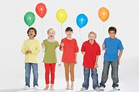 Five children indoors holding balloons and shouting