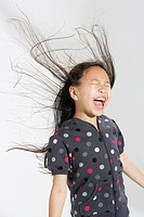 Young girl indoors shouting with hair flying back