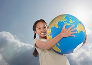 Young girl outdoors holding a large globe