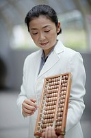 Businesswoman indoors holding abacus