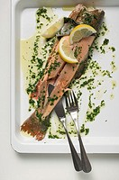 Salmon trout with herb butter and lemon wedges