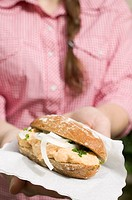 Woman holding bread roll with Obatzda Camembert spread & onions