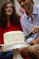 Man cutting coconut cake 4th of July, USA