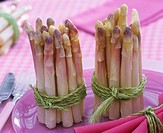 Bundles of white asparagus on purple plate