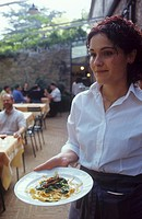 Waitress serving pasta dish, Tuscany, Italy