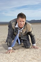 Businessman crawling on dry lake bed