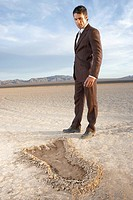 Businessman looking at large footprint in dry lake bed