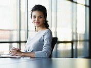 Portrait of businesswoman with papers at conference table