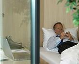 Man using palmtop in bed