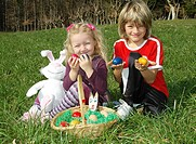 children with Easter nest in meadow
