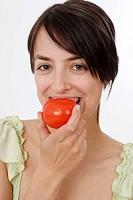 young woman eats tomato
