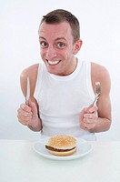 hungry man with burger at plate