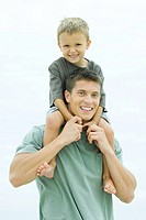 Man carrying son on his shoulders, both smiling at camera, portrait