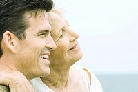 Senior woman and adult son smiling together, cheek to cheek, side view