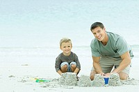 Father and son building sand castle together, both smiling at camera