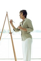 Senior woman painting canvas, side view