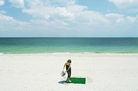 Girl watering square of artificial turf on beach, high angle view