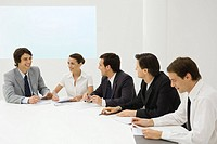 Group of business associates sitting together at conference table, smiling