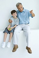 Man sitting with arm around grandson's shoulders, pointing, both looking away