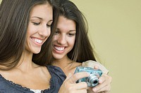 Teenage twin sisters looking at digital camera together, both smiling