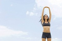 Young woman in sports bra standing with arms raised, low angle view (thumbnail)