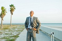 Businessman standing at the beach with hands on hips, smiling, looking away