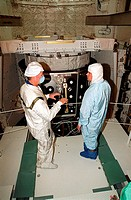 10/02/2000 ___ STS_92 Commander Brian Duffy left talks with a worker during inspection of the payload behind them in Space Shuttle Discovery's payload...