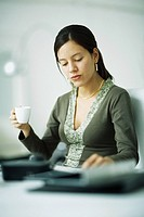 Woman sitting at desk, holding coffee cup, looking down