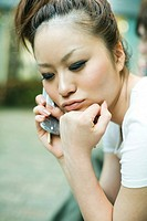Young woman using cell phone, hand under chin, looking down