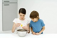 Two young siblings cooking together, girl cracking egg, both looking down