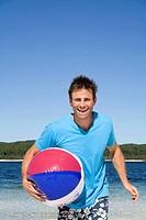 Man on a beach running with a beach ball. Fraser Island, Australia