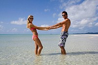 Couple holding hands in the sea. Whitehaven beach, Australia