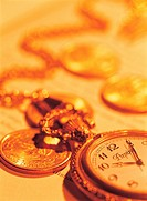 Close-up of Pocket watch and Coins