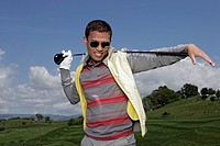 Man wearing shades posing with a golf club over his shoulders