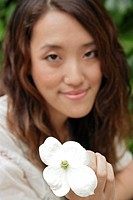 Young woman holding flower, close-up