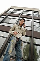One young man using mobile phone, low angle view
