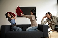Two women fighting with pillows while man observing, side view (thumbnail)