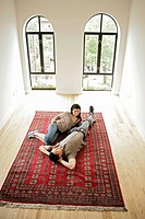 Young couple resting on carpet, high angle view