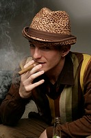 Portrait of a young man smoking a cigar
