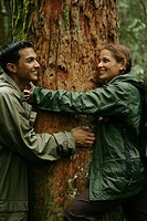 Couple hugging a tree in forest