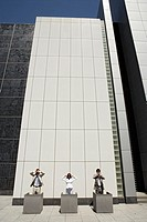Three executives are standing outside an office building